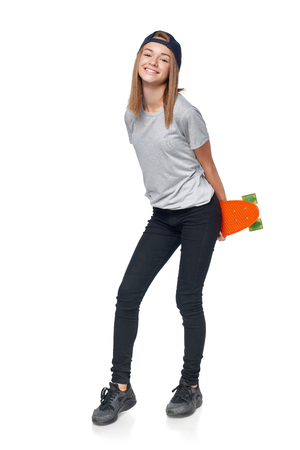 Teen girl in full length holding skate board smiling at camera, isolated on white background