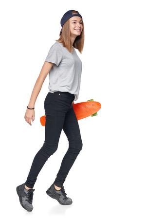Teen girl in full length walking holding skate board , isolated on white background