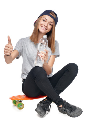 Teen girl in full length sitting on skate board holding a bottle of pure water gesturing thumb up, isolated on white background