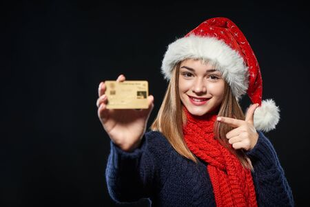 Smiling girl wearing Santa hat showing blank credit card, pointing finger at it over dark background, closeup portrait