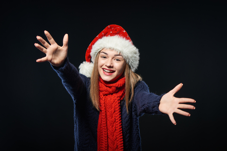 seize: Happy girl wearing Santa hat with outstretched hands to embrace you over dark background