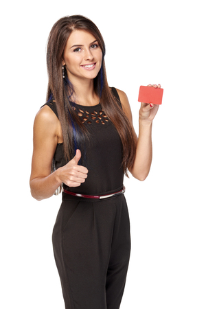Smiling elegant business woman in black standing holding blank credit card and gesturing thumb up, over white background