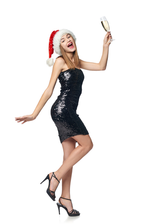 Full length happy Christmas girl in sequined dress and Santa hat holding a glass of champagne dancing Stock Photo