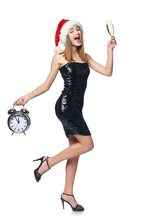 Full length happy Christmas girl in sequined dress and Santa hat jumping of joy with glass of champagne holding alarm clock counting to midnight Stock Photo