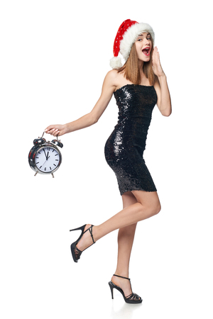 Full length happy Christmas girl in sequined dress and Santa hat running with alarm clock counting to midnight whispering with hand on mouth