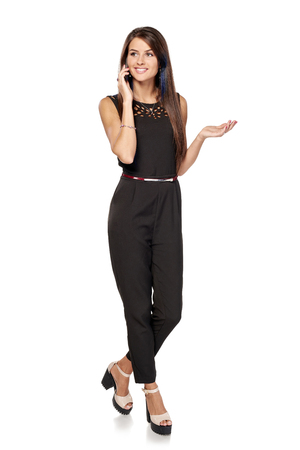 Businesswoman in black standing in full length talking by the smartphone gesticulating over white background looking to side