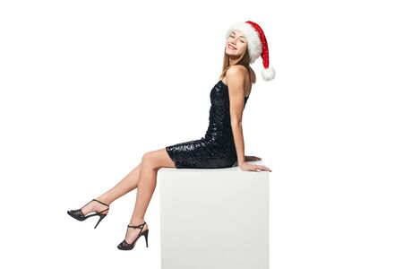 Full length happy Christmas girl in sequined dress and Santa sitting on big white box with blank copy space