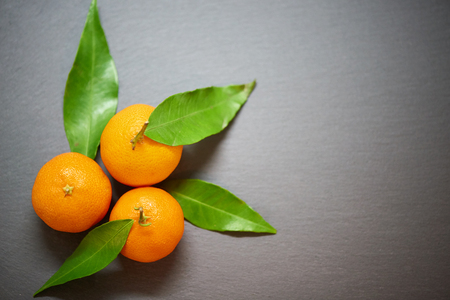 Tangerines with leaves on the slate background, top view Stock Photo