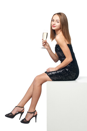 Full length girl in sequined dress holding a glass of champagne sitting on big white box and smiling at camera