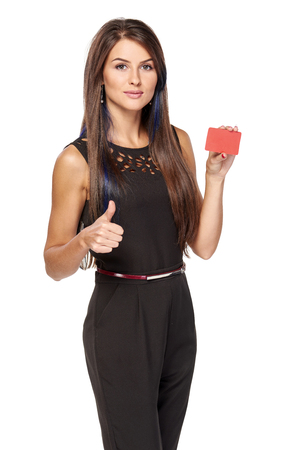 Elegant business woman in black standing holding blank credit card and gesturing thumb up, over white background