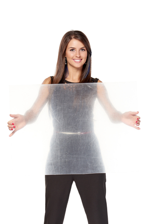 Woman holding transparent sheet of plastic, over white background