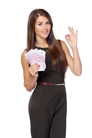 Business woman with euro money in hand showing approval gesture, over white background