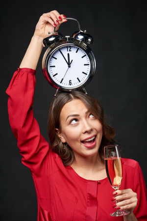Time to celebrate. Happy woman in red shirt and wavy hair holding a glass of champagne and big clock, over dark background