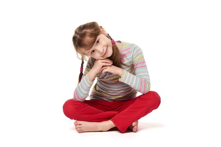 Smiling little girl sitting on floor with crossed legs in a lotus pose leaning on elbows, isolated on white background Stock Photo