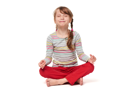 Little girl sitting on floor with crossed legs in a lotus pose trying to meditate and smiling, isolated on white background Stock Photo