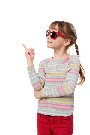 Child girl in sunglasses standing in full length looking to side thinking, isolated on white background