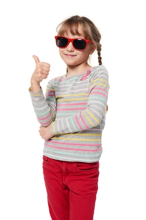 Child girl in sunglasses gesturing thumb up, isolated on white background