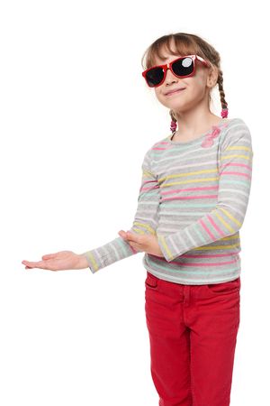 Child girl in sunglasses showing to side at blank copy space for your text or product, isolated on white background Stock Photo