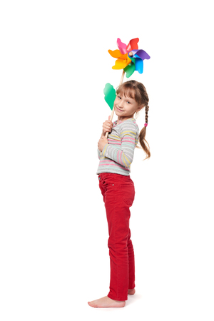 Little girl with colorful windmill standing in full length over white background