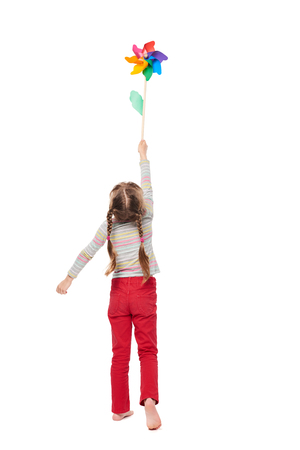 Back view of little girl standing in full length lifting colorful windmill over white background