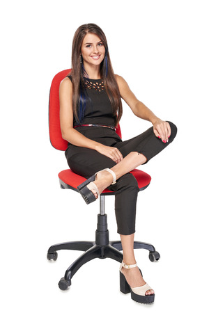 Smiling woman in black sitting on office chair smiling at camera, full length portrait