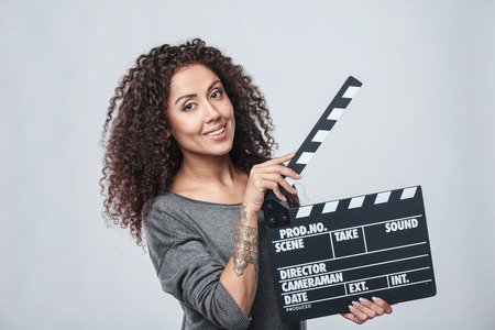 Smiling curly female holding movie clapper board, slate film. Stock Photo