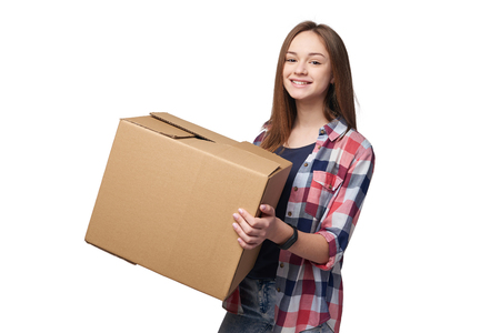 Delivery, relocation and unpacking. Smiling young woman holding cardboard box isolated on white background Фото со стока