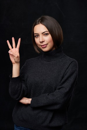 Smiling woman in grey turtleneck sweater over dark background showing three fingers