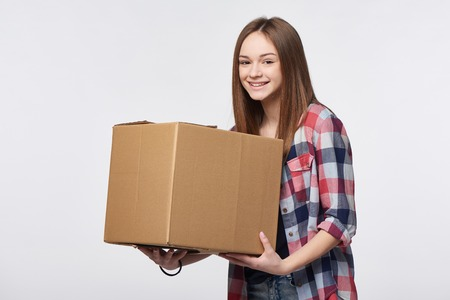 Delivery, relocation and unpacking. Smiling young woman holding cardboard box isolated Zdjęcie Seryjne
