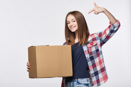 Delivery, relocation and unpacking. Happy young woman holding cardboard box pointing at box with copy space