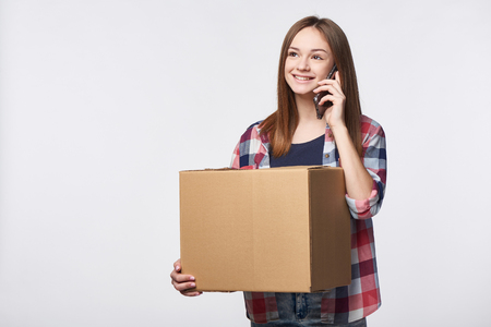 Delivery, relocation and unpacking. Smiling young woman holding cardboard box and talking on cellphone looking away at blank copy space. Call center and customer support service concept.
