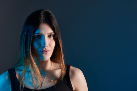 Closeup of young woman on dark background with blue backlit Stock Photo
