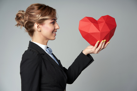 Side view of business woman holding red polygonal paper heart shape