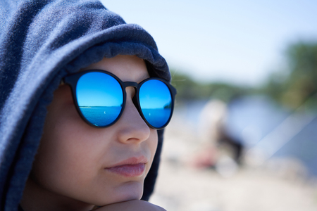 Closeup of pensive little girl in a hood and sunglasses looking away in thoughts with reflection of river in glasses