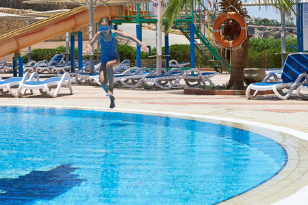 Little girl jumping in outdoor swimming pool