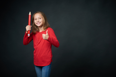 Lovely girl with big pencil gesturing thumb up, ready for school