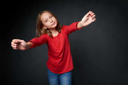 School age girl stretching arms holding imaginary banner copy space over dark studio background