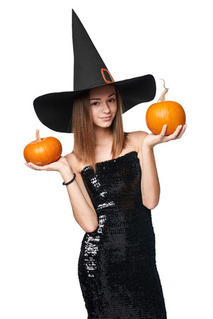 Smiling Halloween witch holding orange pumpkins, isolated on white background