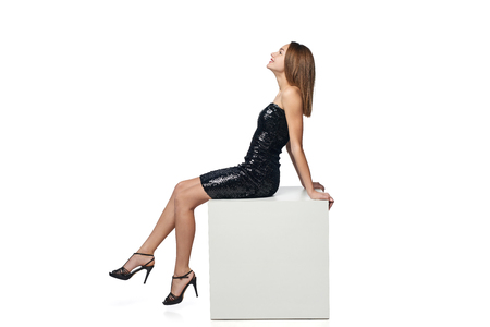Side view portrait of full length happy girl in sequined dress sitting on big white box with blank copy space looking forward, isolated on white background