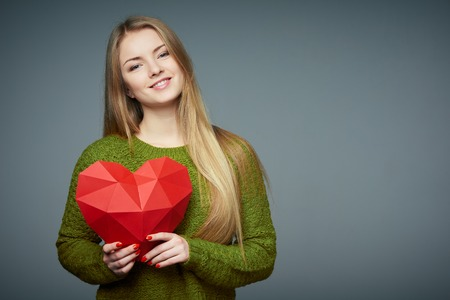 Portrait of beautiful blond girl in sweater looking at camera smiling holding red polygonal paper heart shape on grey studio background