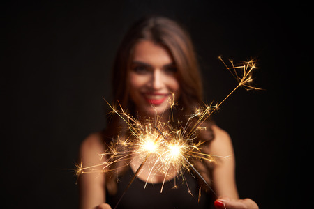 Party, drinks, holidays and celebration concept. Woman with sparklers in hands. Shallow depth of field, focus on lights Stock Photo
