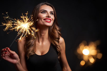 Party, holidays and celebration concept. Closeup of a woman with sparklers in hands looking aside playful happy, over dark background