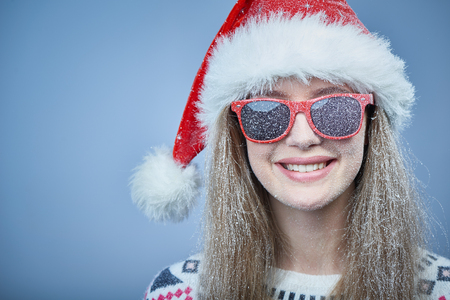 Closeup of frozen girl with snow on face wearing Santa hat and sunglasses, looking at camera smiling Stock Photo