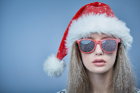 Closeup of frozen girl with snow on face wearing Santa hat and sunglasses, looking at camera Stock Photo