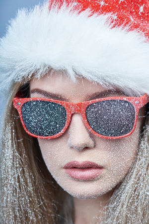Closeup of frozen girl with snow on face wearing Santa hat and sunglasses, looking at camera Stock fotó