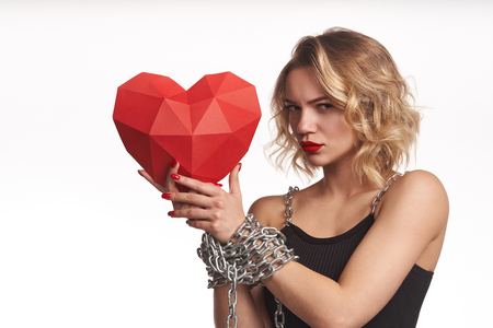 Love hostage concept. Woman holding red polygonal paper heart shape with tied by chain hands