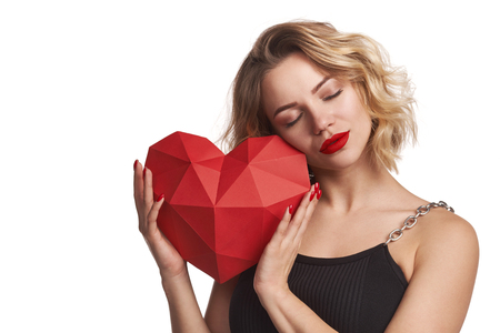 Beautiful woman holding red polygonal paper heart shape enjoying with closed eyes, isolated on white