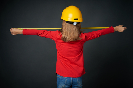 Decoration, renovation and reconstruction concept. Back view of a girl wearing construction safety helmet using a measuring tape Imagens