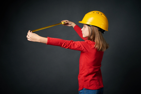 Decoration, renovation and reconstruction concept. Side view of a girl wearing construction safety helmet using a measuring tape