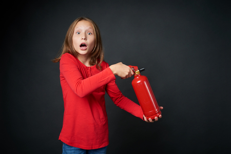 Shocked girl holding red fire extinguisher directing at blank copy space, over dark background Foto de archivo